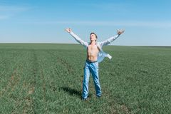 A young attractive sporty man in a white shirt and blue jeans stands in the field. royalty free stock photo