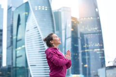 Young attractive sporty woman in namaste mudra pose. Young sporty model wearing pink sportswear practicing yoga near the skyscraper, namaste mudra pose, dreaming Stock Image