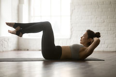 Young attractive sporty woman practicing Sit Ups exercise, studi Royalty Free Stock Image