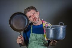Young attractive stressed and overwhelmed lazy man with apron holding kitchen pan and cook pot in stress and frustrated b. Ackground in domestic work and messy royalty free stock images