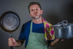 Young attractive stressed and overwhelmed lazy man with apron holding kitchen pan and cook pot in stress and frustrated b. Ackground in domestic work and messy royalty free stock image