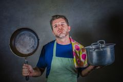 Young attractive stressed and overwhelmed lazy man with apron holding kitchen pan and cook pot in stress and frustrated b. Ackground in domestic work and messy stock images