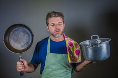 Young attractive stressed and overwhelmed lazy man with apron holding kitchen pan and cook pot in stress and frustrated b. Ackground in domestic work and messy stock photography
