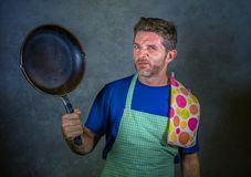 Young attractive stressed and overwhelmed lazy man with apron holding kitchen pan in stress and frustrated face expression isolate. Young attractive stressed and stock photos