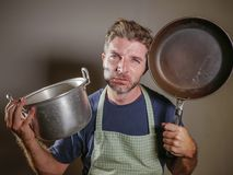 Young attractive stressed and overwhelmed lazy man with apron holding kitchen pan in stress and frustrated face expression isolate. D background in domestic work royalty free stock images