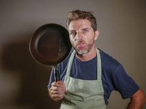 Young attractive stressed and overwhelmed lazy man with apron holding kitchen pan in stress and frustrated face expression isolate. D background in domestic work royalty free stock image