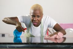 Young attractive stressed and upset back african American woman washing kitch detergent spray bottle and cloth cleaning home kitch stock photography