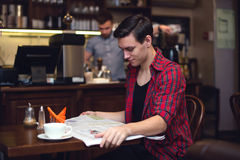 Young attractive student drinking coffee and. Reading newspaper in the cafe with barista on the backside Stock Photos