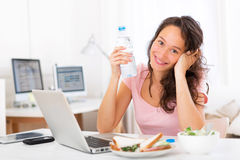 Young attractive student drinking water while working Royalty Free Stock Image
