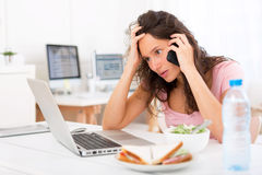 Young attractive student eating salad while phoning Royalty Free Stock Images