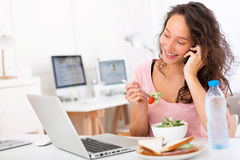 Young attractive student eating salad while phoning Stock Photo