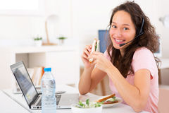 Young attractive student  eating sandwich while working Royalty Free Stock Photos