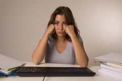 Young attractive student girl or working woman sitting at computer desk in stress looking tired exhausted and boring Royalty Free Stock Image