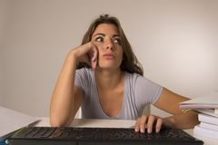 Young attractive student girl or working woman sitting at computer desk in stress looking tired exhausted and boring Stock Images
