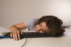 Young attractive student girl or working woman sitting at computer desk in stress sleeping tired exhausted and boring. Taking a nap in overwork job and Stock Photos