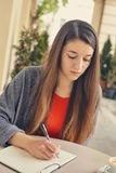 Young attractive student in red dress studying and reading a book. Relax, rest, education concept, recreation Royalty Free Stock Photography