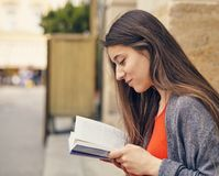 Young attractive student in red dress studying and reading a book. Relax, rest, education concept, recreation Stock Photos