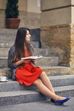 Young attractive student in red dress studying and reading a book. Relax, rest, education concept, recreation Royalty Free Stock Images