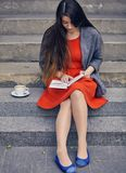 Young attractive student in red dress studying and reading a book. Relax, rest, education concept, recreation Stock Photo