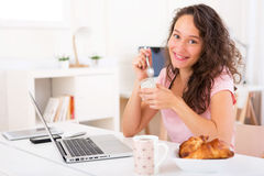 Young attractive student taking breakfast while working Stock Photo