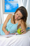 Young attractive student woman with apple in nightgown. Young attractive and beautiful woman in nightgown lying on bed at bedroom holding apple writing diary Stock Photography