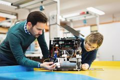Young attractive students of mechatronics working on project Stock Photography