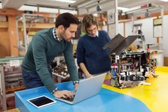 Young attractive students of mechatronics working on project Stock Images