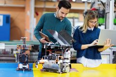 Young attractive students of mechatronics working on project Royalty Free Stock Images