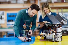 Young attractive students of mechatronics working on project Stock Photos
