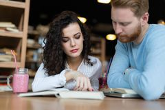 Young students spending time in coffee shop reading books Stock Photo