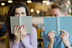 Young students spending time in coffee shop reading books Royalty Free Stock Photo