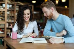 Young students spending time in coffee shop reading books. Young attractive students spending time in coffee shop reading books Stock Image