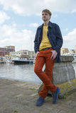 Young attractive stylish blond man against canal background. Stock Photos