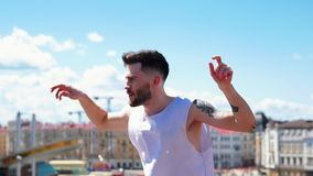 Young attractive stylish man with tattoos freestyle dancing on the top point in the centre of the city stock video