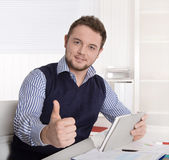 Young attractive successful manager with thumb up at office. Stock Photography