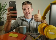 Young attractive and successful self employed business man using mobile phone sending text working at modern home office hispter s. Tyle in freelance sucess Stock Image
