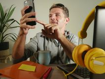 Young attractive and successful self employed business man using mobile phone sending text working at modern home office hispter s. Tyle in freelance sucess and royalty free stock images