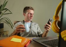 Young attractive and successful self employed business man using mobile phone sending text working at modern home office hispter s. Tyle in freelance sucess and stock photography
