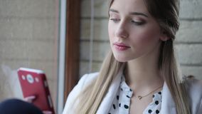 Young attractive successful woman looking at something on her mobile phone in the light office near the window. stock video