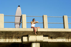 Young attractive surfer girl sitting on pier with surfboard Stock Photography
