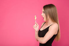 Young attractive surprised woman with lollipop Royalty Free Stock Images