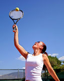 Young attractive tanned healthy woman playing tennis in midday sun with blue sky