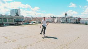 A young attractive tattooed man dancing on the roof on the background of the city center. Mid shot stock video footage