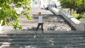 A young attractive tattooed man dancing on the stairs outdoors. A young attractive tattooed man dancing on the stairs on the outdoors - mid shot stock footage