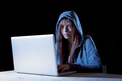 Young attractive teen woman wearing hood on hacking laptop computer cybercrime cyber crime concept Royalty Free Stock Photography