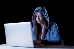 Young attractive teen woman wearing hood on hacking laptop computer cybercrime cyber crime concept Stock Images