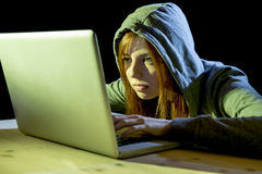 Young attractive teen woman wearing hood on hacking laptop computer cybercrime cyber crime concept Royalty Free Stock Photo
