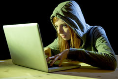 Young attractive teen woman wearing hood on hacking laptop computer cybercrime cyber crime concept Royalty Free Stock Image