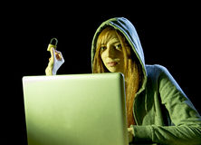 Young attractive teen woman wearing hood on hacking laptop computer cybercrime cyber crime concept. Young attractive teen woman wearing hood on looking dark and royalty free stock photography