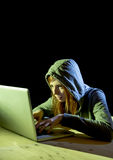 Young attractive teen woman wearing hood on hacking laptop computer cybercrime cyber crime concept Stock Photography